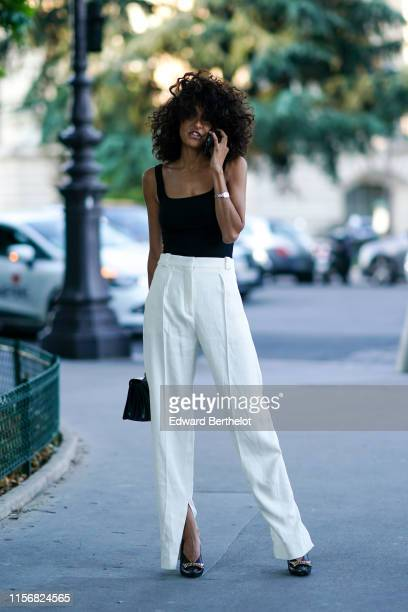 A guest wears a black strappy tank top white pants a silver bangle black heeled pumps outside AMI during Paris Fashion Week Menswear Spring/Summer...