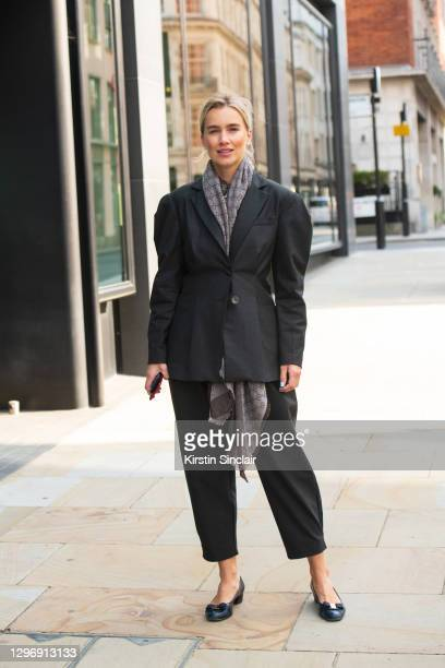 Guest wears a black suit, Gucci scarf and navy ballet pumps during LFW September 2020 on September 19, 2020 in London, England.