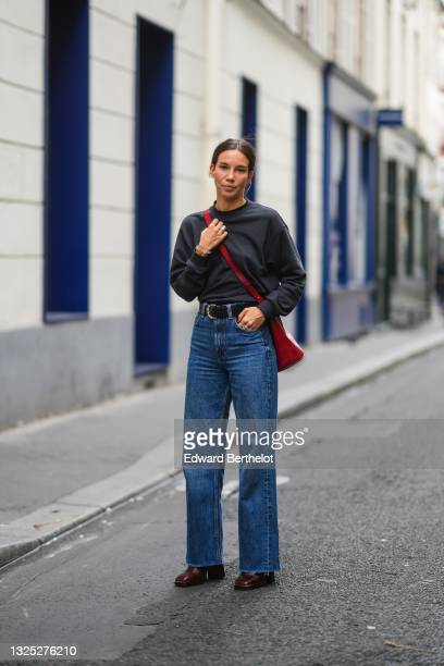 Guest wears a black sweater, silver rings, a red shiny leather crossbody bag, a black shiny leather crocodile pattern with silver buckle belt, blue...