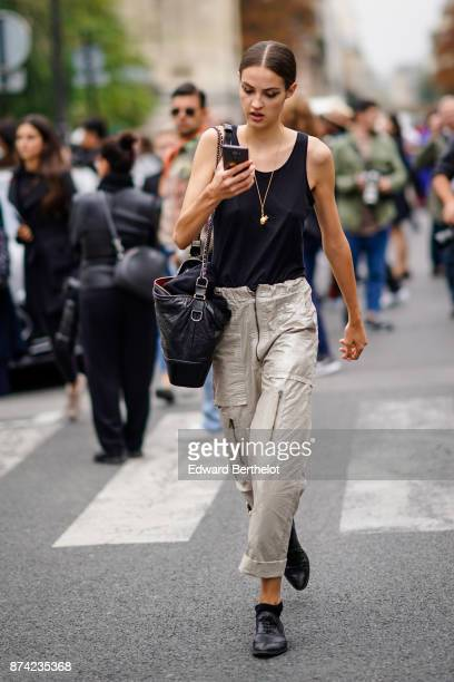 A guest wears a black tank top gray cropped pants outside Lanvin during Paris Fashion Week Womenswear Spring/Summer 2018 on September 27 2017 in...