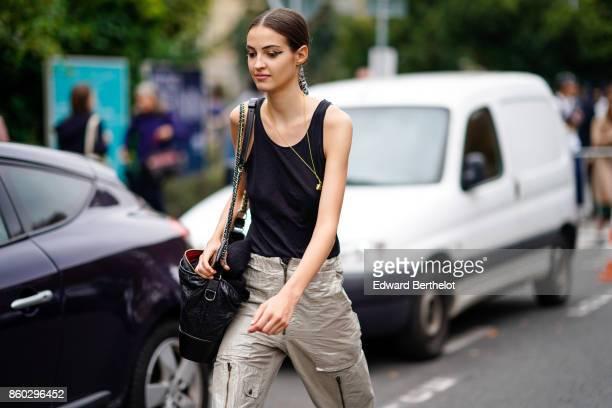 A guest wears a black top a black bag multizip beige pants outside Lanvin during Paris Fashion Week Womenswear Spring/Summer 2018 on September 27...