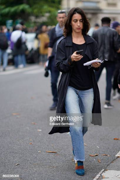A guest wears a black top a black trenchcoat ripped blue jeans royal blue suede boots with tawny yellow and brown empiecements outside Lanvin during...