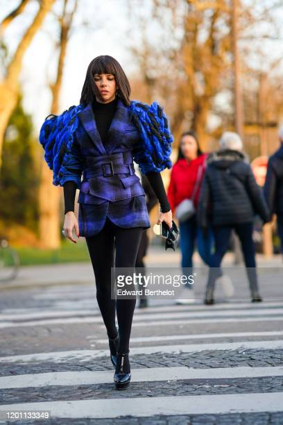 A guest wears a black top a purple and black checkered jacket decorated with blue and black wool braids a matched mini skirt black opaque tights...