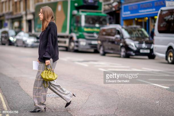 A guest wears a black top a yellow bag gingham flare pants outside JW Anderson during London Fashion Week September 2017 on September 16 2017 in...
