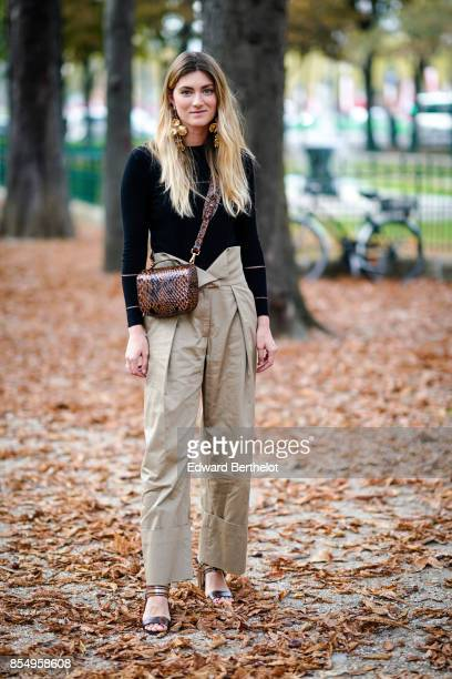 A guest wears a black top beige pants a leather bag outside the Rochas show during Paris Fashion Week Womenswear Spring/Summer 2018 on September 27...