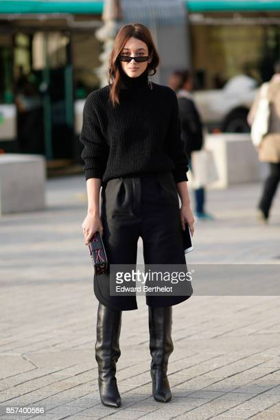 A guest wears a black top black cropped pants black boots outside Louis Vuitton during Paris Fashion Week Womenswear Spring/Summer 2018 on October 3...