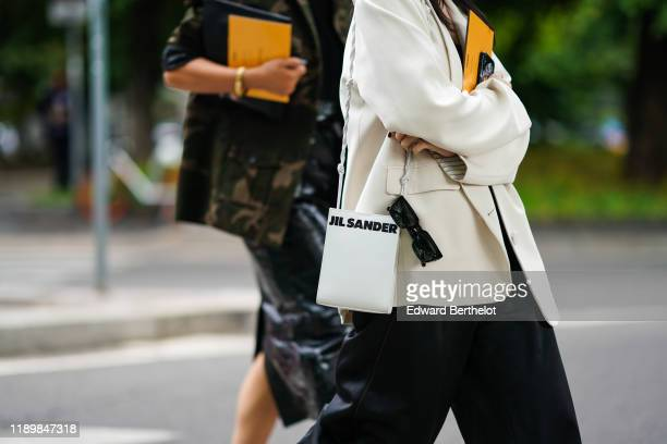 Guest wears a black top, black pants, a cream-color jacket, a white Jil Sanders bag, outside the Fendi show during Milan Fashion Week Spring/Summer...