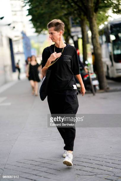 A guest wears a black top black pants white sneakers outside 1017 ALYX 9SM during Paris Fashion Week Menswear SpringSummer 2019 on June 24 2018 in...