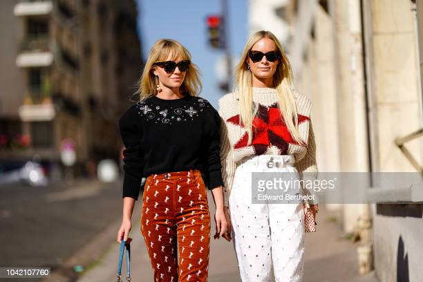 A guest wears a black top red pants a guest wears a woll pullover white flare pants outside Chloe during Paris Fashion Week Womenswear Spring/Summer...