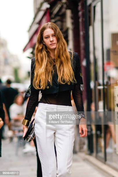 A guest wears a black top white pants outside Givenchy during Paris Fashion Week Haute Couture Fall Winter 2018/2019 on July 1 2018 in Paris France