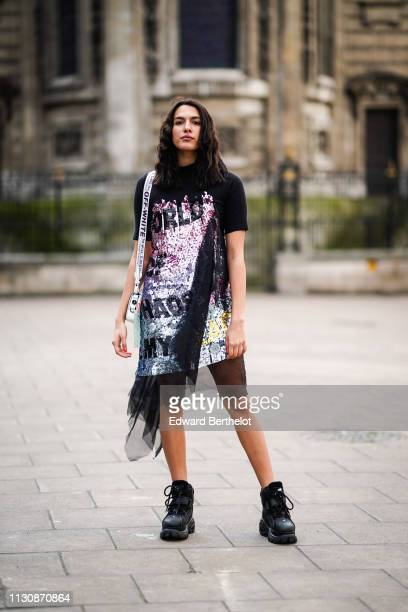 A guest wears a black top with printed multicolor glitter sequin features an OffWhite bag during London Fashion Week February 2019 on February 19...