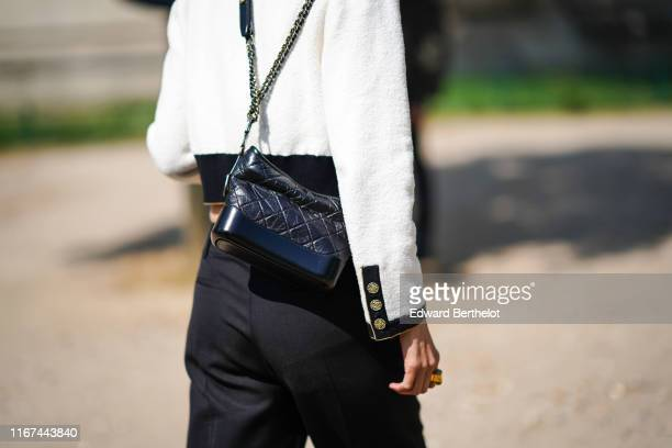 A guest wears a black trimmed white Chanel jacket a black Chanel bag outside the Chanel Cruise Collection 2020 At Grand Palais on May 03 2019 in...