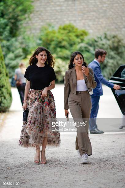 A guest wears a black tshirt a lace skirt with colored embroidered flowers a guest wears a blazer jacket a white top flared pants sneakers shoes...