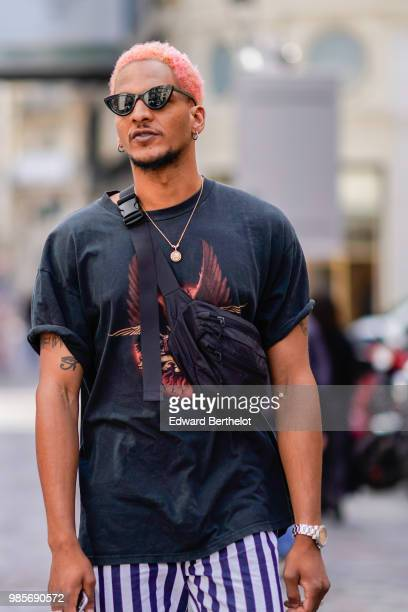 A guest wears a black tshirt a shoulder strap bag sunglasses outside Christian Dada during Paris Fashion Week Menswear SpringSummer 2019 on June 24...