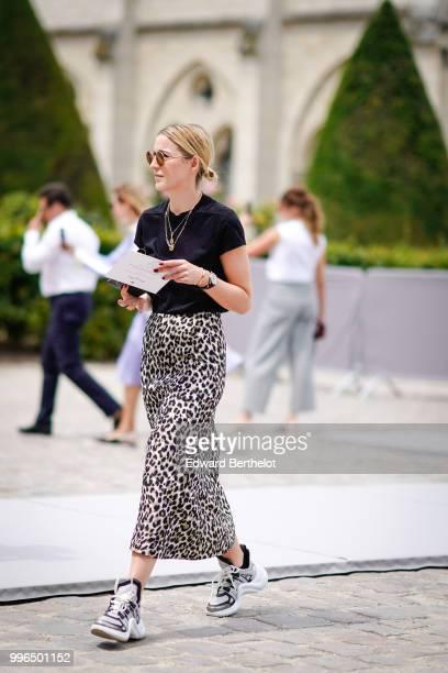 A guest wears a black tshirt sunglasses a necklace a leopard print skirt Vuitton sneakers shoes outside Dior during Paris Fashion Week Haute Couture...