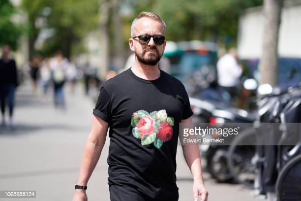 A guest wears a black tshirt with printed roses outside Rick Owens during Paris Fashion Week Menswear SpringSummer 2019 on June 21 2018 in Paris...