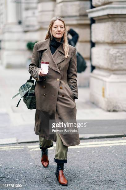 A guest wears a black turtleneck a brass buttons brown trench coat a green bag khaki cuffed pants brown and black pointy boots during London Fashion...