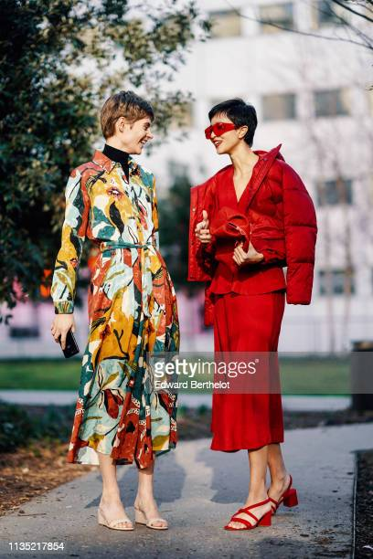 A guest wears a black turtleneck a colorful floral print pleated shirtdress beige see through mules a guest wears red sunglasses a red bag a red...