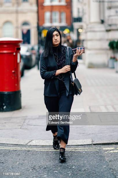 A guest wears a black turtleneck a navy blue jacket a black top with small white dots navy blue wide leg pants a black bag black shiny shoes during...