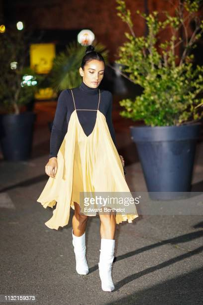 Guest wears a black turtleneck, a yellow dress, white boots, outside Jacquemus, during Paris Fashion Week Womenswear Fall/Winter 2019/2020, on...