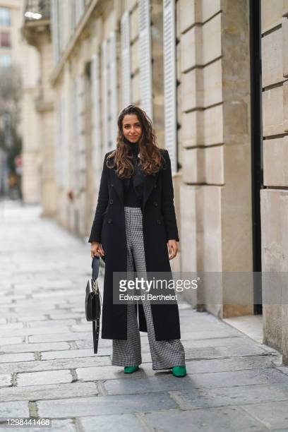 Guest wears a black turtleneck pullover, a black jacket, a black wool long coat, black and white houndstooth pattern printed flared pants, a black...