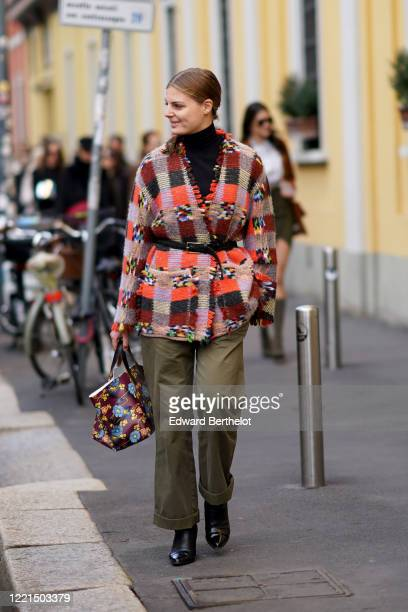 Guest wears a black turtleneck pullover, a colorful checked wool vest, a floral print leather bag, green pants, black leather boots, outside Tod's,...
