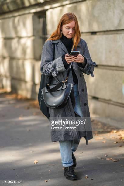 Guest wears a black turtleneck pullover, blue faded denim jeans pants, a gray long coat, a black shiny leather large Hortensia Handtasche handbag...