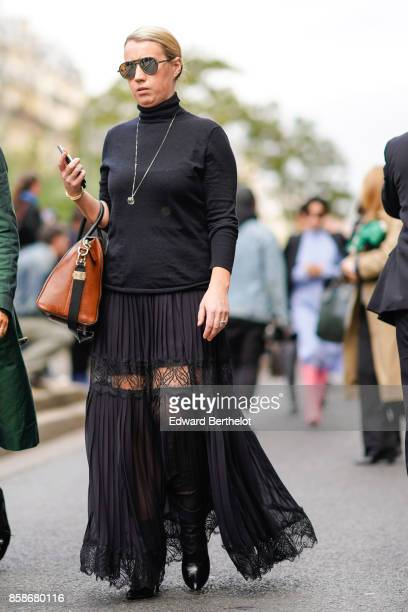 A guest wears a black turtleneck top a black pleated lace mesh skirt black leather boots a brown bag outside Giambattista Valli during Paris Fashion...