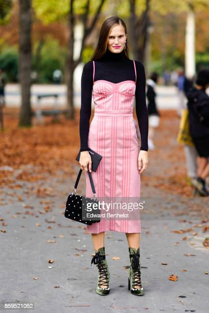 A guest wears a black turtleneck top a pink striped strapless dress a black studded bag green velvet laceup platform shoes outside the Rochas show...