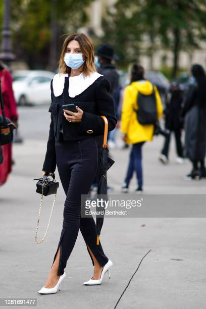 Guest wears a black tweed jacket with white large collar, black slit pants, white high heeled pointy shoes, a black bag, outside Chanel , during...