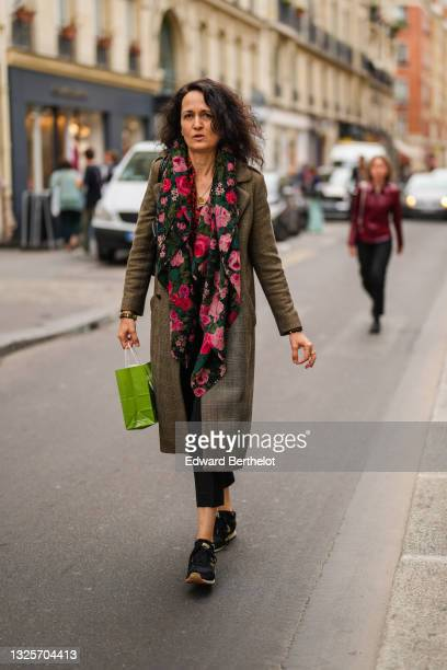 Guest wears a black with red green and pink roses flower patterns scarf, a long brown and beige checkered coat, a black and gold bracelet, a gold...