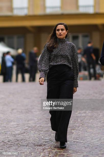 Guest wears a black with white polka dots turtleneck flowing shirt with puffy shoulder, black flowing pants, black shiny leather block heels shoes,...