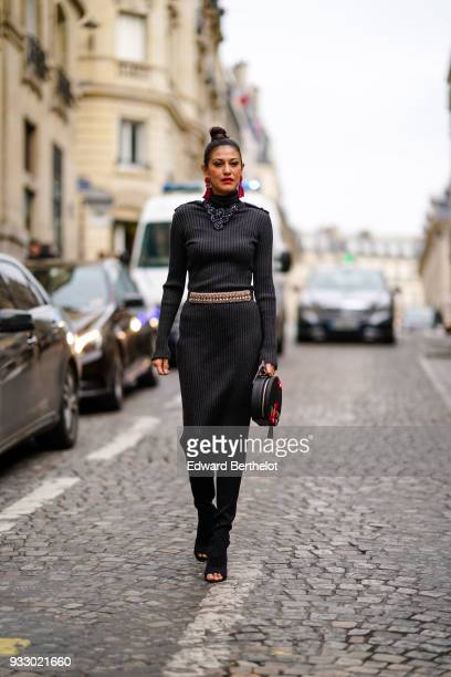 A guest wears a black wool dress a belt a round bag with red printed flowers during Paris Fashion Week Womenswear Fall/Winter 2018/2019 on March 3...