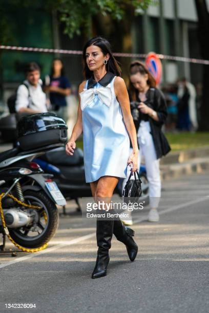 Guest wears a black wool felt beret / hat, black sunglasses, a pale blue shiny silk short dress with a black collar and a white and rhinestones...