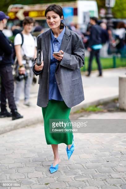 A guest wears a blazer jacket a blue shirt a green pleated skirt blue shoes outside Elie Saab during Paris Fashion Week Womenswear Spring/Summer 2018...