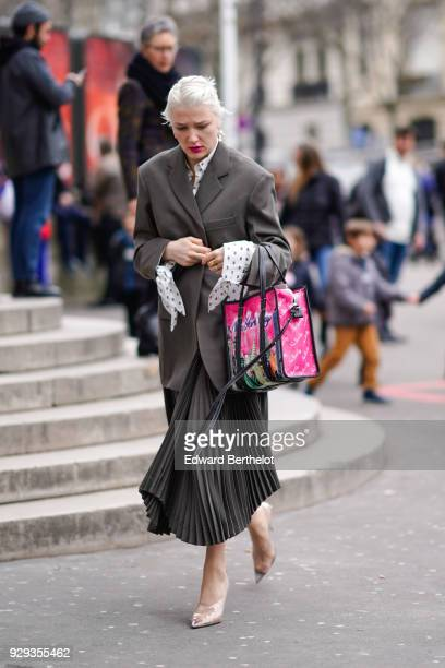 A guest wears a blazer jacket a pink bag a pleated skirt shoes during Paris Fashion Week Womenswear Fall/Winter 2018/2019 on March 6 2018 in Paris...