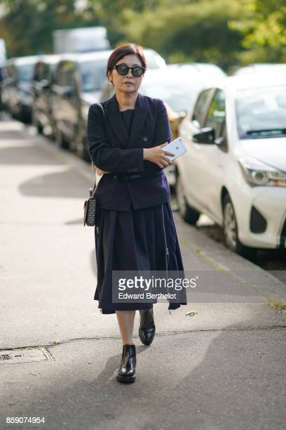 A guest wears a blazer jacket a pleated skirt sunglasses black shoes outside CDG Comme des Garcons during Paris Fashion Week Womenswear Spring/Summer...