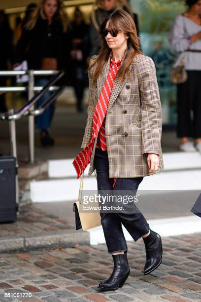A guest wears a blazer jacket a red tie cropped pants black shoes outside Preen by Thornton Bregazzi during London Fashion Week September 2017 on...