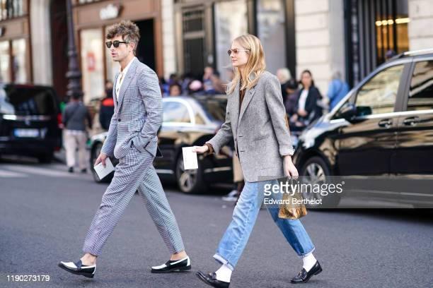 Guest wears a blazer jacket, a snake print bag, blue denim jeans, black leather shoes, outside Balmain, during Paris Fashion Week - Womenswear Spring...