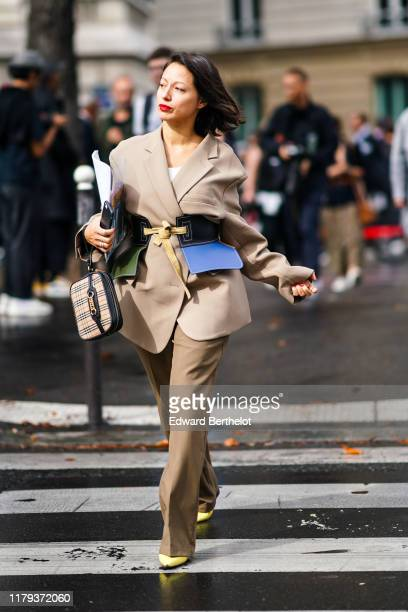 A guest wears a blazer jacket a tartan checkered bag flared beige pants yellow pointy shoes a colorful corset outside Miu Miu during Paris Fashion...