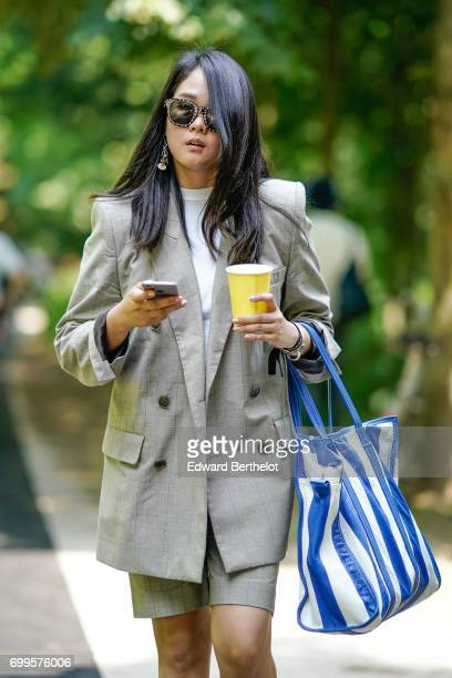 A guest wears a blazer jacket and a striped bag outside the Balenciaga show during Paris Fashion Week Menswear Spring/Summer 2018 on June 21 2017 in...