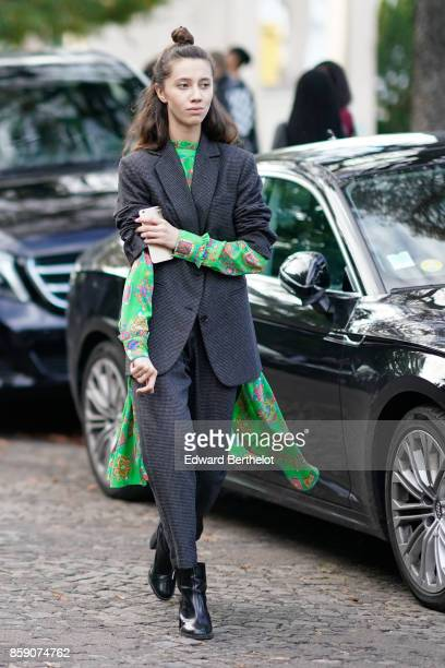 A guest wears a blazer jacket over a green floral print dress black leather shoes outside CDG Comme des Garcons during Paris Fashion Week Womenswear...
