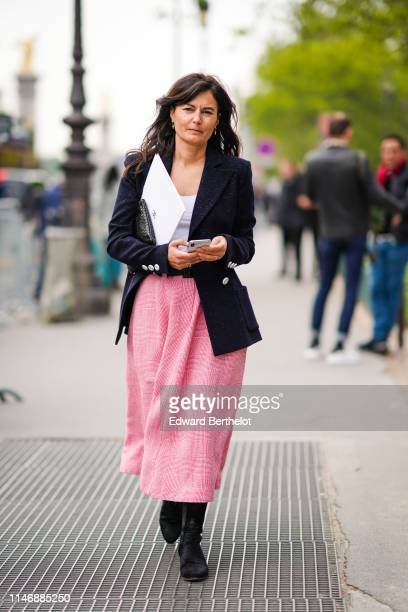 A guest wears a blazer jacket with buttons a white top a pink skirt outside the Chanel Cruise Collection 2020 At Grand Palais on May 03 2019 in Paris...