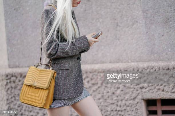 A guest wears a blazer jacket with fabric pattern and a yellow squared bag outside the Kenzo show during Paris Fashion Week Menswear Spring/Summer...
