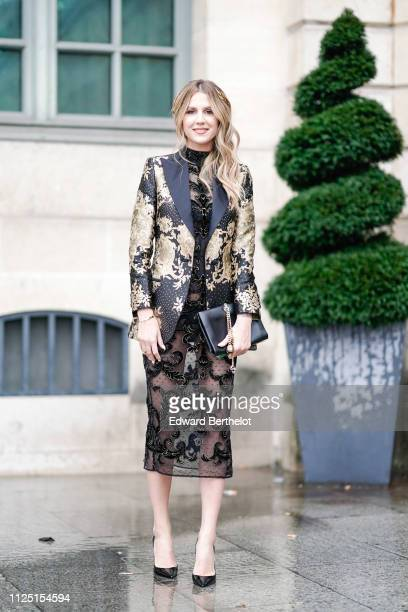 A guest wears a blazer jacket with golden floral print a black lace dress outside Alexis Mabille during Paris Fashion Week Haute Couture Spring...