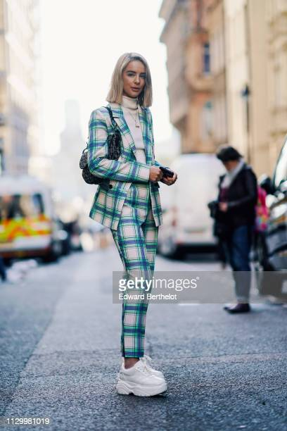 A guest wears a blue and white checked blazer jacket and pants white sneakers during London Fashion Week February 2019 on February 15 2019 in London...