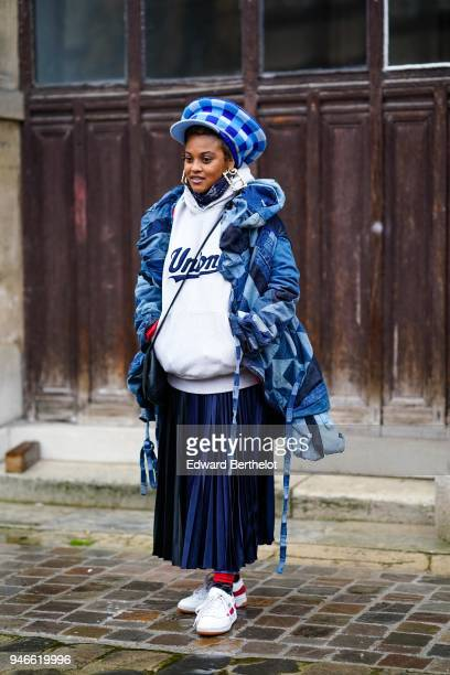 A guest wears a blue and white checked hat a white hoodie sweater a blue coat a blue pleated skirt sneakers shoes outside Thom Browne during Paris...