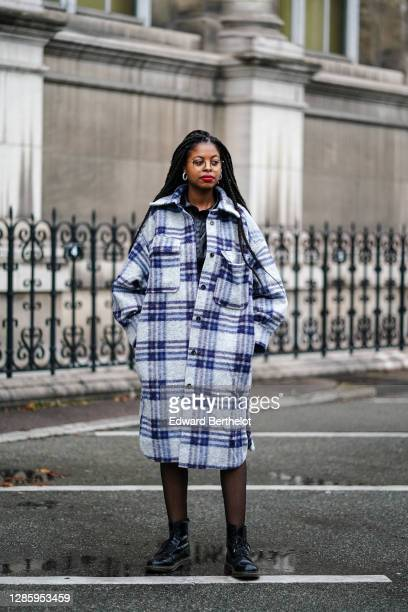 Guest wears a blue and white checked long wool coat with large pockets, black tights, black leather Dr Martens shoes, outside Yohji Yamamoto, during...