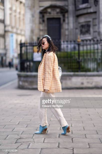 A guest wears a blue and white headband sunglasses a yellow and white checkered jacket beige fluid pants blue python pattern pointy boots during...