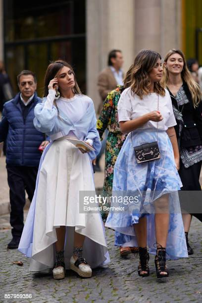 A guest wears a blue and white pleated large dress a guest wears a white tshirt a blue skirt a Prada bag black shoes outside Miu Miu during Paris...